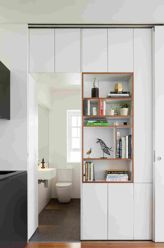 a doorway with open shelves and sleek cabinets right in the doorway is a cool idea to separate a small bathroom from another room