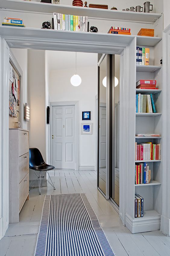 a doorway with open shelves coering the whole space over it is a cool idea to store some things and use the unused space