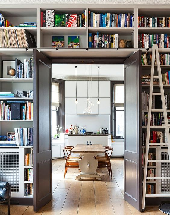 a doorway with open shelves over the door and around it is like organizing a whole library around the door without wasting floor space