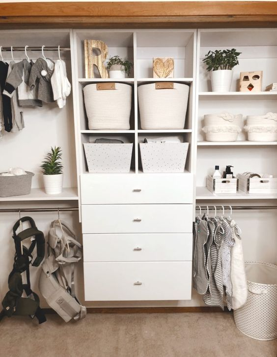 a large closet with a dresser, fabric baskets, planters and clothes hangers looks neat and chic