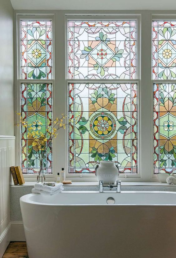 a large stained glass bathroom window is a beautiful vintage-inspired feature and a chic statement for a space