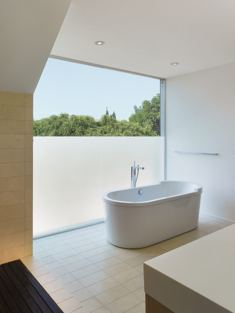 a minimalist neutral bathroom with a panoramic window, partly with frosting to enjoy the views but keep the space private