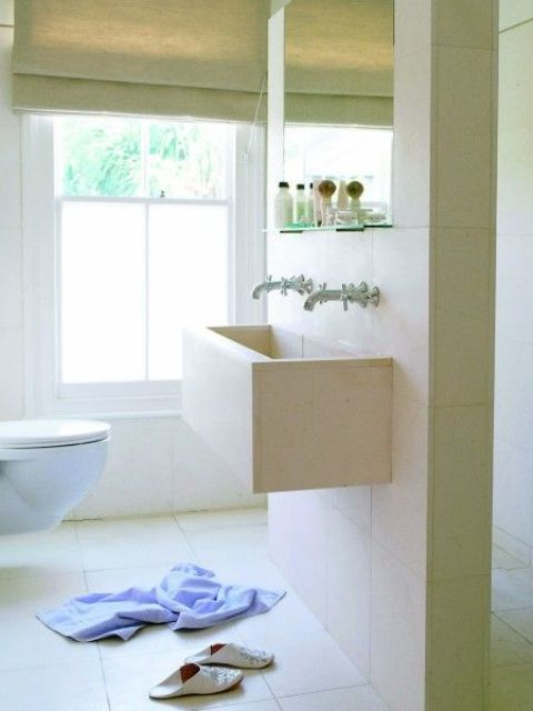 a minimalist neutral bathroom with partly frosted windows that keep it private but still bring much light inside