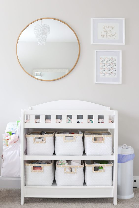 a modern white changing table with fabric baskets to organize some stuff and store it comfortably