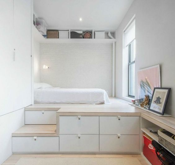 a platform bed with storage drawers is a cool solution for a small bedroom, add an open shelf over it
