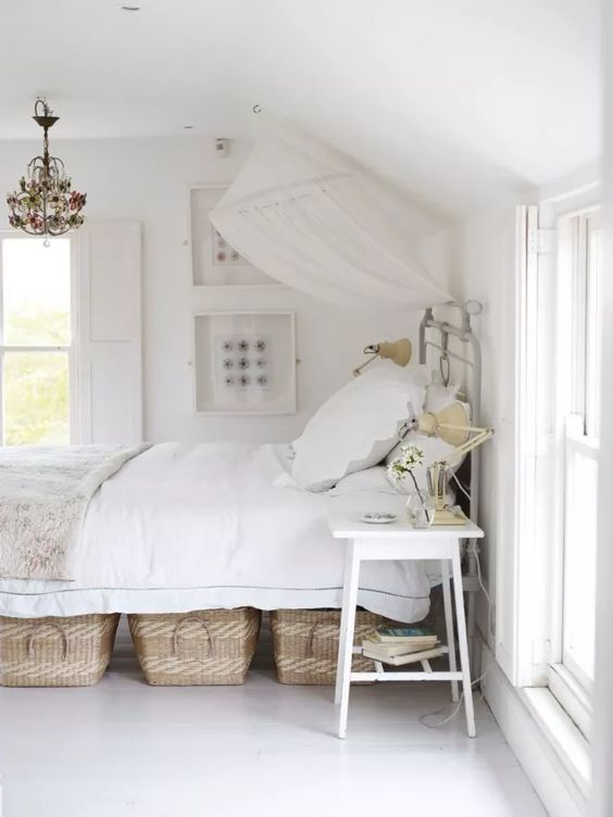 a pretty white bed with some woven baskets for storage is a nice option for those who don't have a ready storage bed