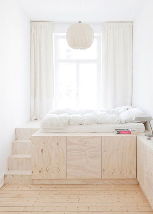 a risen bed with large hidden storage units inside it is a lovely idea for a tiny bedroom