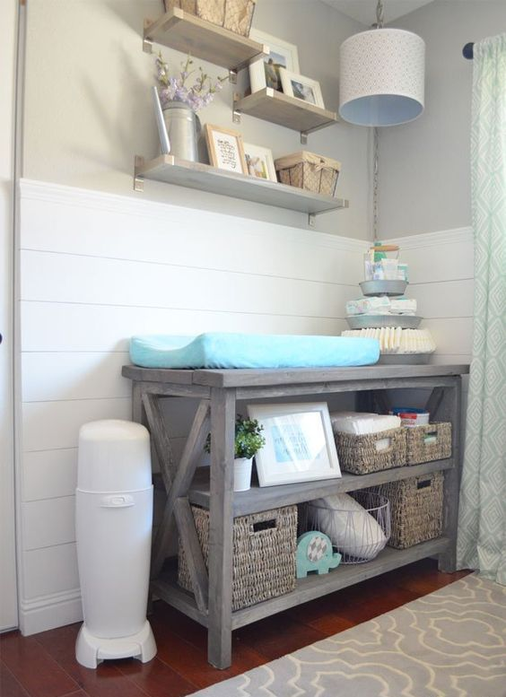 a rustic changing table with basket boxes for storage and organization