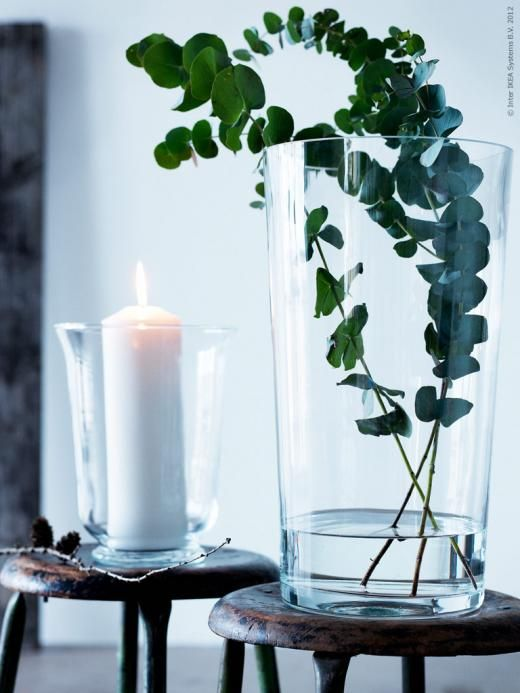 a simple spring decor idea - a glass with a candle and a vase with eucalyptus plus some twigs