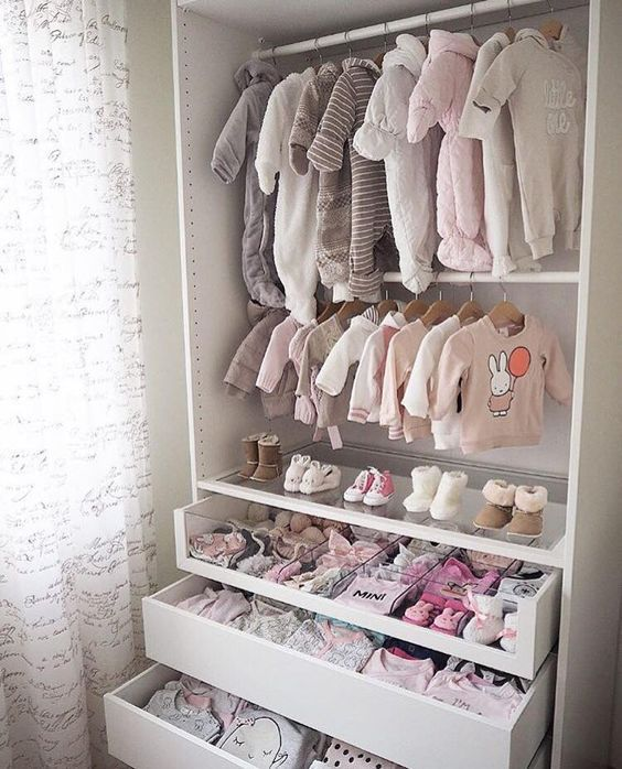 a small and cute closet with baby's clothes on hangers, drawers and a glass drawer with compartments to organize