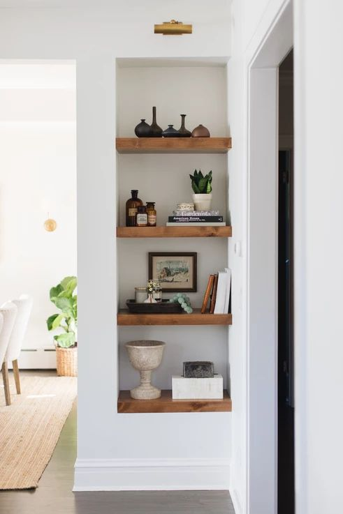 a small awkward nook by the doorway taken by niche shelves with various cool accessories and plants is a great idea to rock