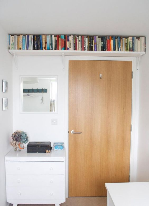 a small bookshelf over the doorway allows to store a lot of books and not to clutter the small space at the same time