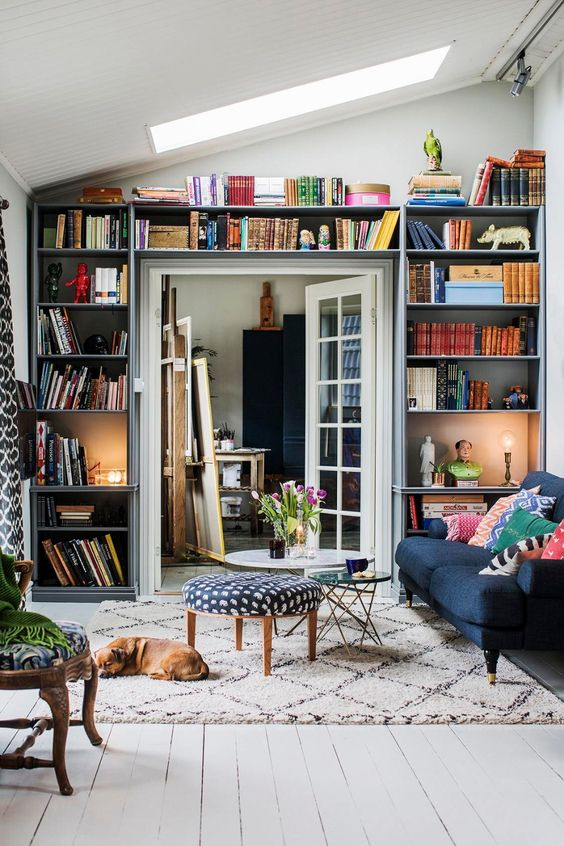 a small living room with open shelves taking a whole wall with the door - a smart idea that allows to store a lot of things here