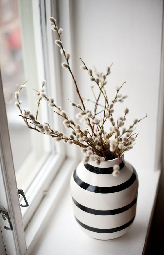 a striped black and white vase with willow is a lovely spring decoration in Nordic style