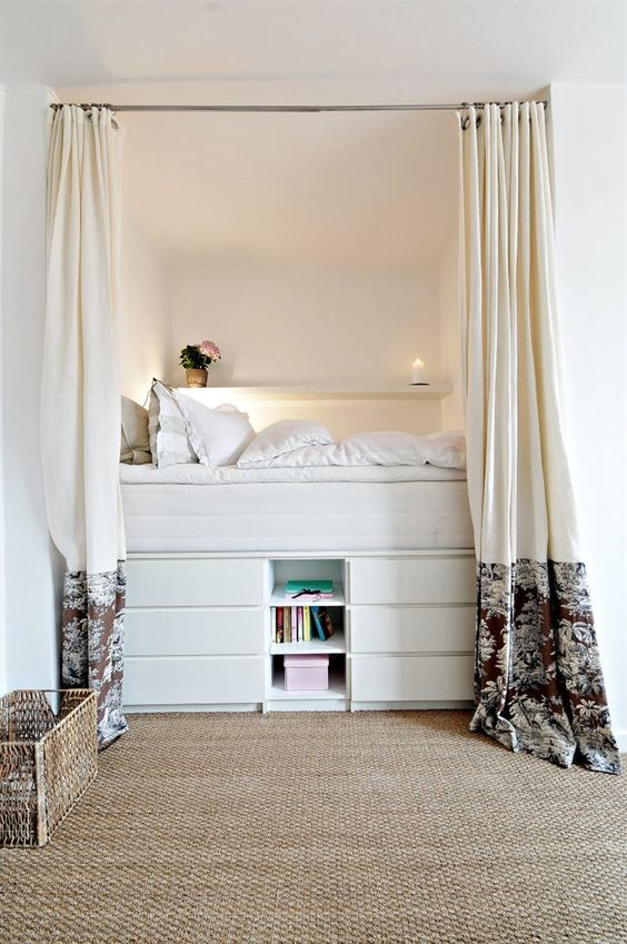 a tall bed built of several layers of drawers and open storage ocmpartments is a cozy and functional unit