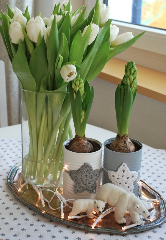 a tray with lights, bears, bulbs in tin cans with crochet stars and white tulips in a vase for a Nordic feel