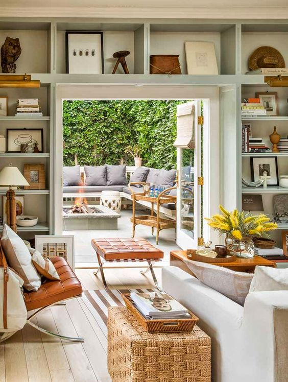 a welcoming neutral living room with open shelves over the doorway for displaying things, books and other stuff is a cool idea to save some space