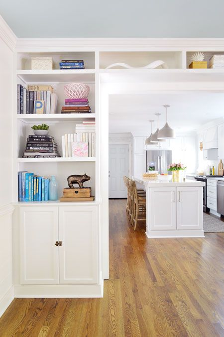 a wide doorway surrounded by open shelves and cabinets is a cool idea to store a lot of things and declutter your spaces
