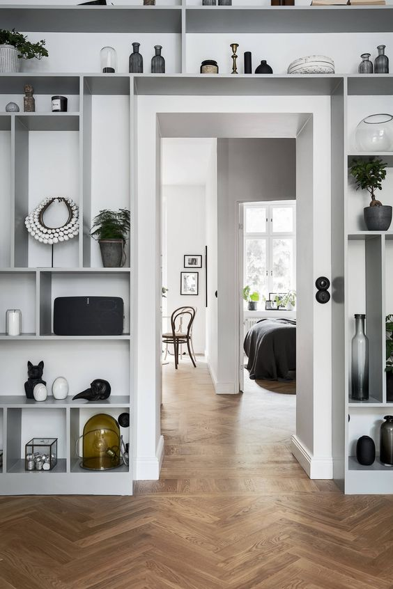 all the space around the doorway take by an open shelving unit display art, candleholders, potted plants and various accessories