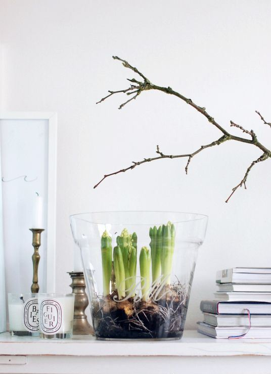 an easy spring decor idea - branches and a glass with bulbs plus candles all around for a Scandinavian feel