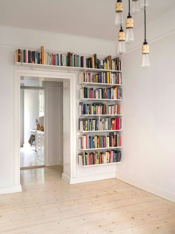 bookshelves covering one wall next to the doorway and a space over it will give you much space for books and will help you declutter the space