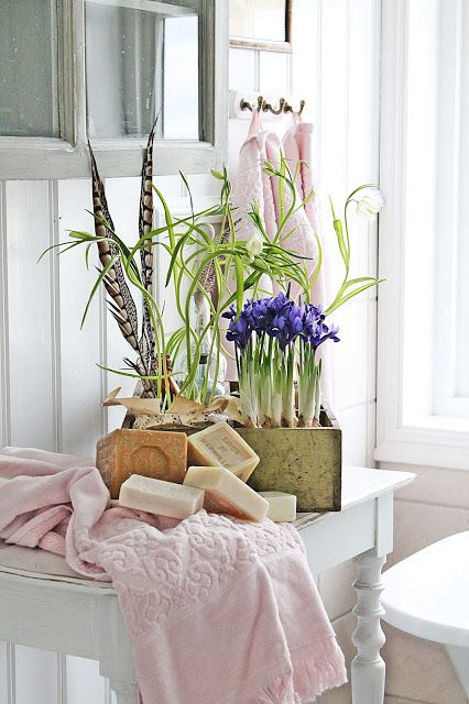 cool Scandinavian bathroom decor with a box with bulbs and greenery, feathers and stacks of soap pieces