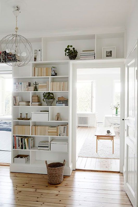 doorways with open shelves taking the wall and the space over them is a cool idea to store books and potted plants is a cool idea