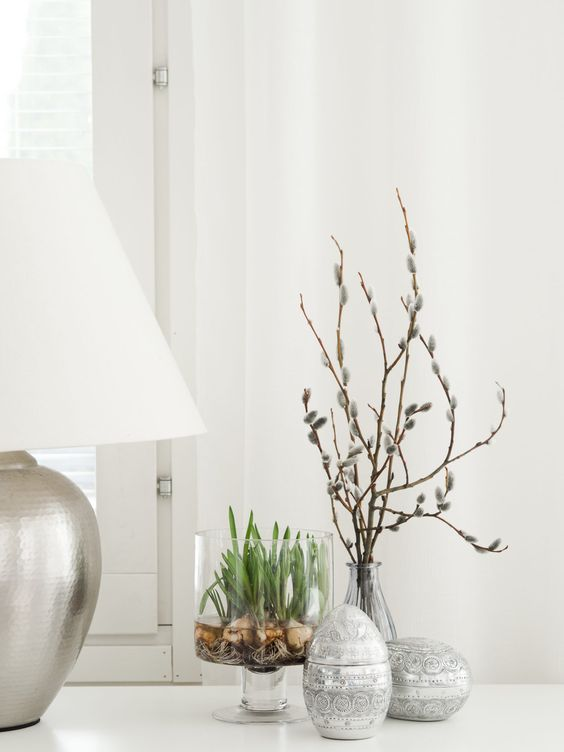 easy Scandinavian spring decor with patterned eggs, a glass with bulbs and willow in a vase