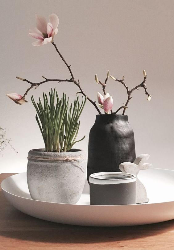 elegant Nordic spring decor with a bowl with a concrete planter with greenery, a black vase with cherry blossom, a candle and a bunny