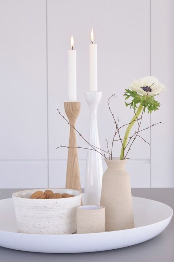 minimal Nordic decor with a tray with a bowl with nuts, candles in simple candlesticks and a vase with a bloom and branches