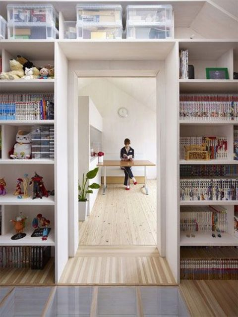 open shelves surrounding the doorway are used for storing kids' stuff - books, toys and other things in boxes is a smart idea to organize the space