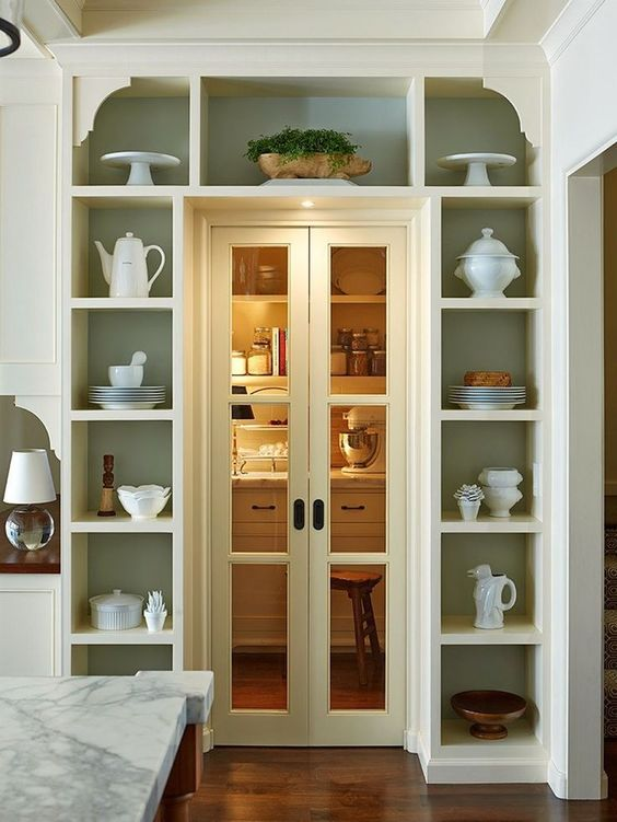 open shelves surrounding the doorway display pretty tableware and teaware and show off some potted plants are a super cool idea