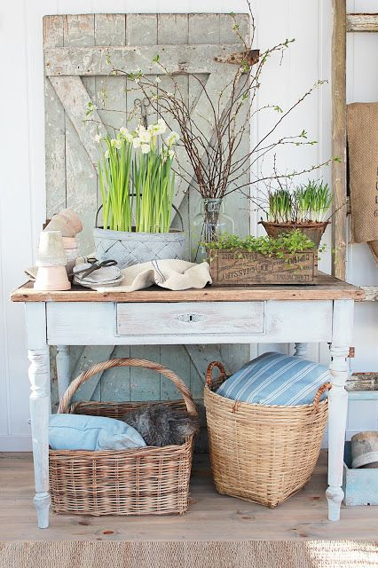 rustic Scandinavian spring decor with a wooden plaque, potted bulbs and greenery, blooming branches and linens