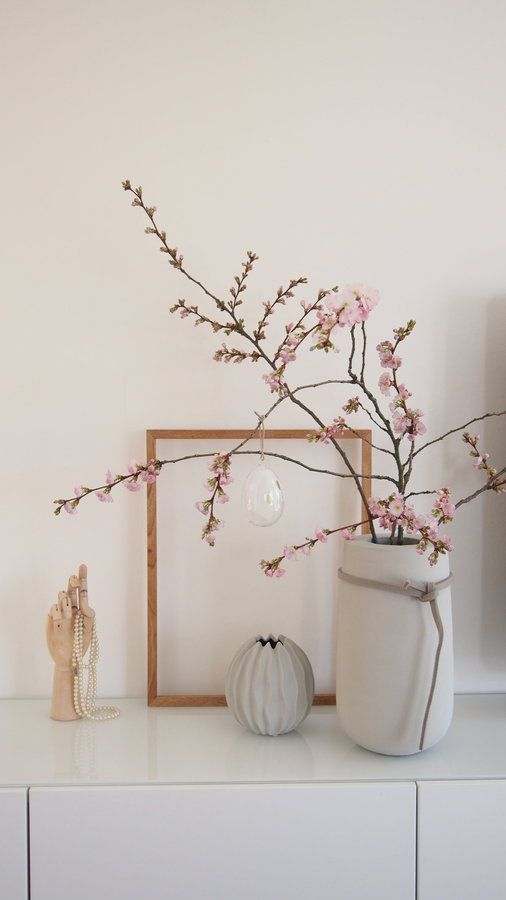 simple Nordic spring decor wiht a decorative vase and a large concrete one with blooms plus a sheer egg