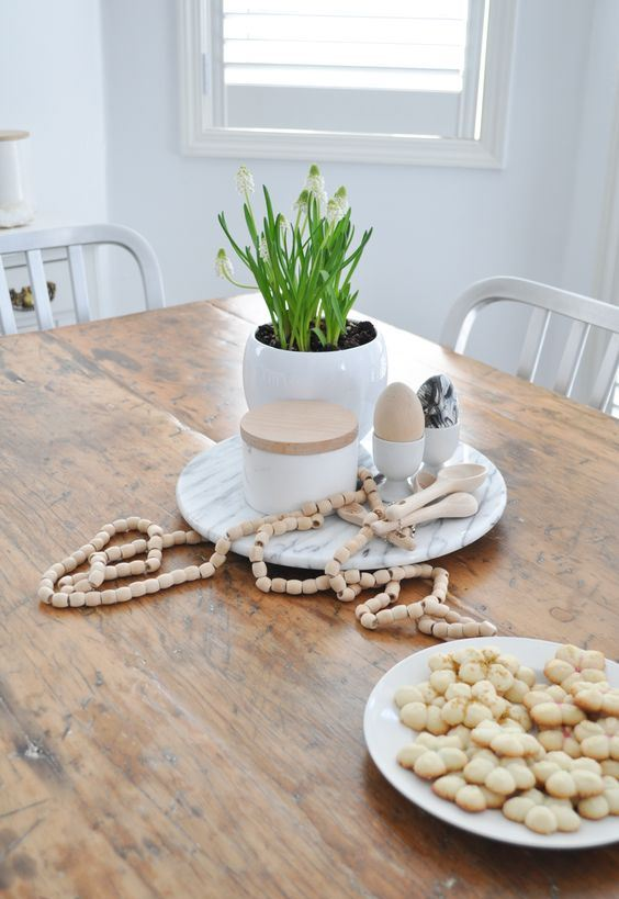 simple Nordic spring decor with an egg-shaped planter with bulbs, eggs in egg stands and wooden beads for Easter