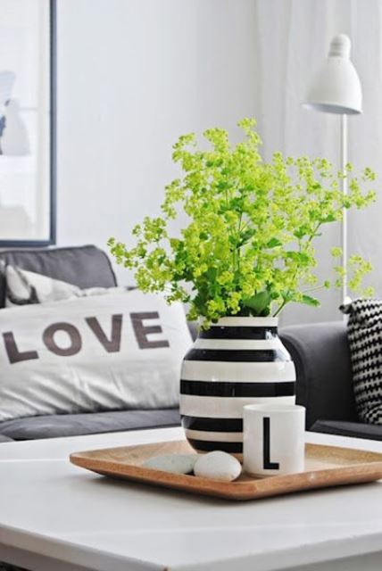 simple and cool Scandinavian decor with a wooden tray with pebbles, a mug and a striped vase with green blooms