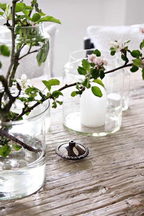 spring Scandinavian decor with a vase with vases with candles, a glass vase with blooming branches