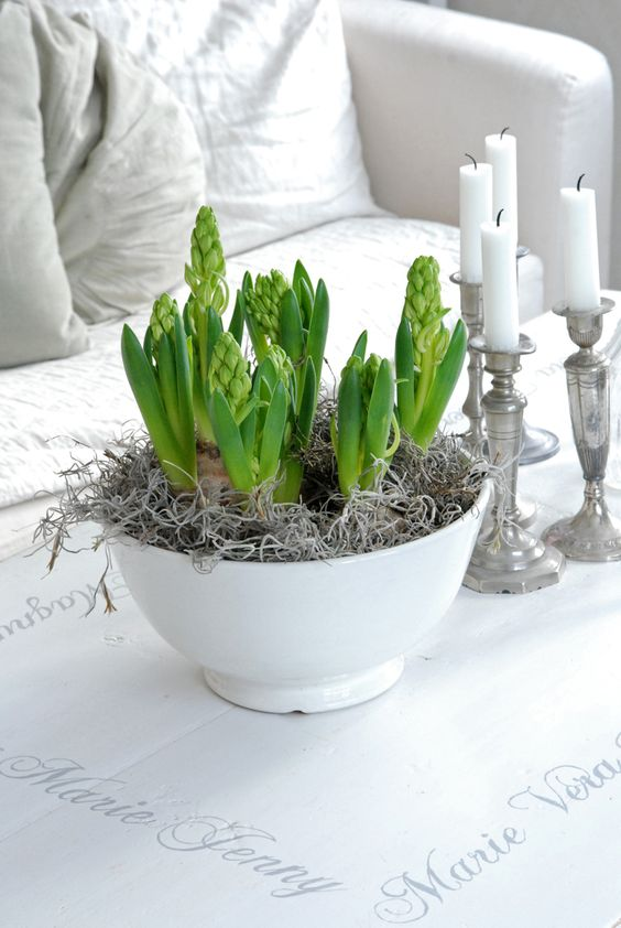 vintage spring decor with candles in silver candleholders, a bowl with hay and bulbs for a Scandinavian feel