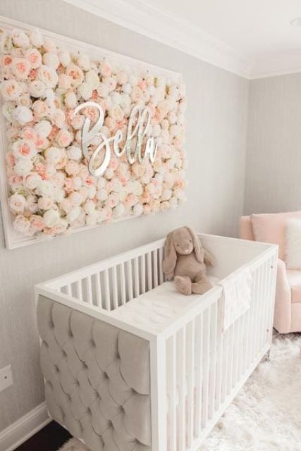 a beautiful girl nursery with light grey walls, white and pink furniture, a floral artwork and neutral bedding