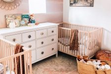 a boho desert nursery with a watercolor wall, neutral and white furniture, a desert artwork, Moroccan leather ottomans