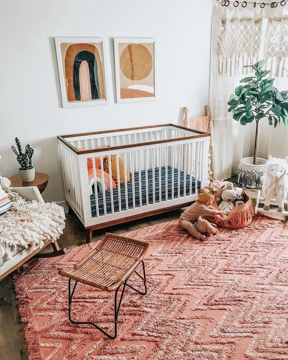 a boho nursery with a bright red ru, boho hangings, mid century modern artworks and fluffy touches