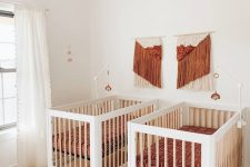 a boho twin nursery in white, with rust and orange touches, with printed bedding, a rattan chandelier and fringe artworks
