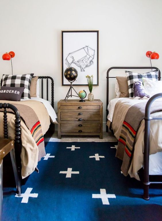a bold shared teen boy bedroom with black beds, layered rugs, bright bedding, a gallery wall and red sconces