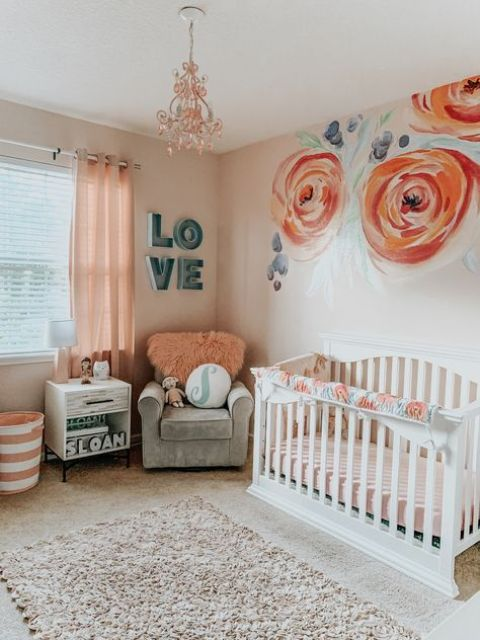 a bright and cool girl nursery with painted flowers, white and grey furniture, peachy pink bedding and a lovely coral chandelier
