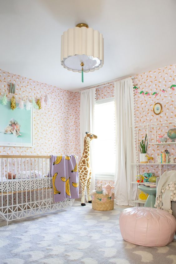 a bright and fun tropical nursery with pink floral wallpaper, white furniture, pink and purple touches and fun toys