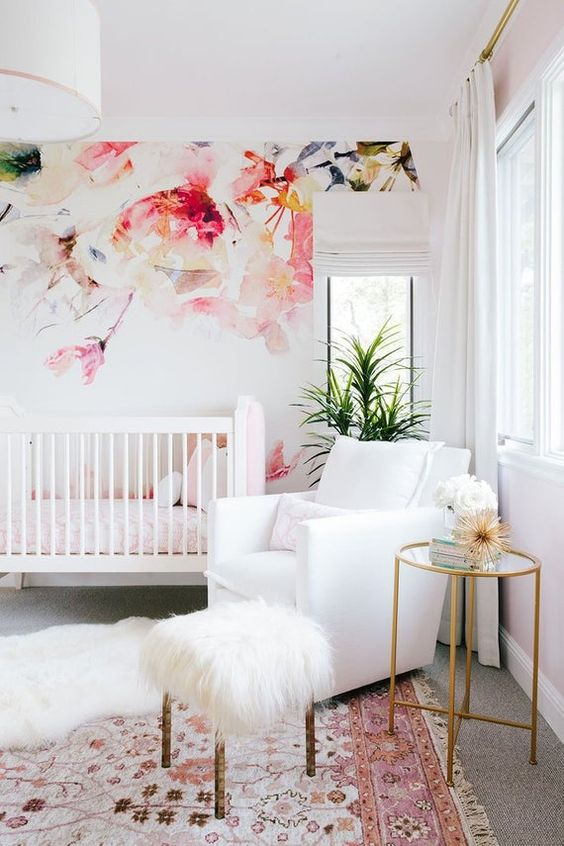 a bright girlish nursery with a bold floral accent wall, white furniture, a bold printed rug, a mini side table and potted plants