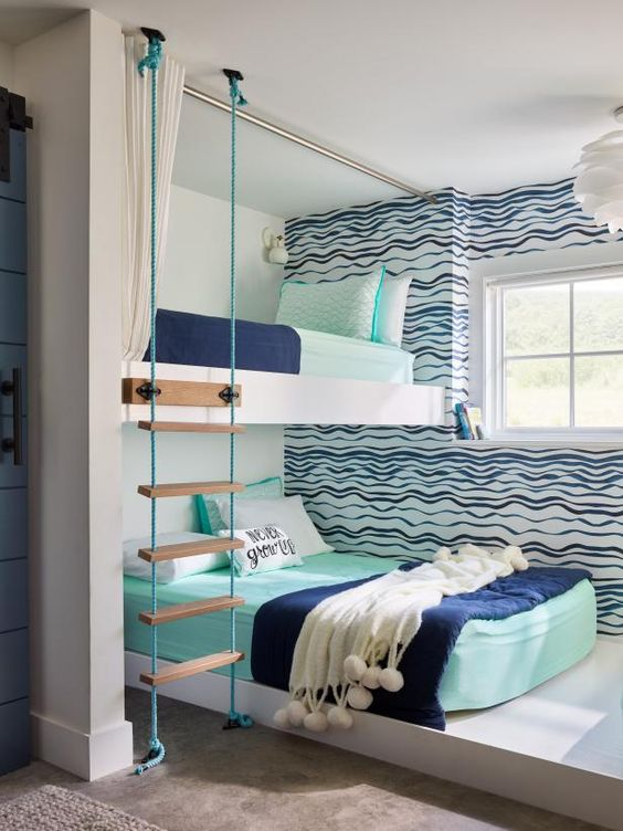 a bright seaside-inspired shared boy bedroom with an accent wall, a bunk bed, a ladder and bright bedding