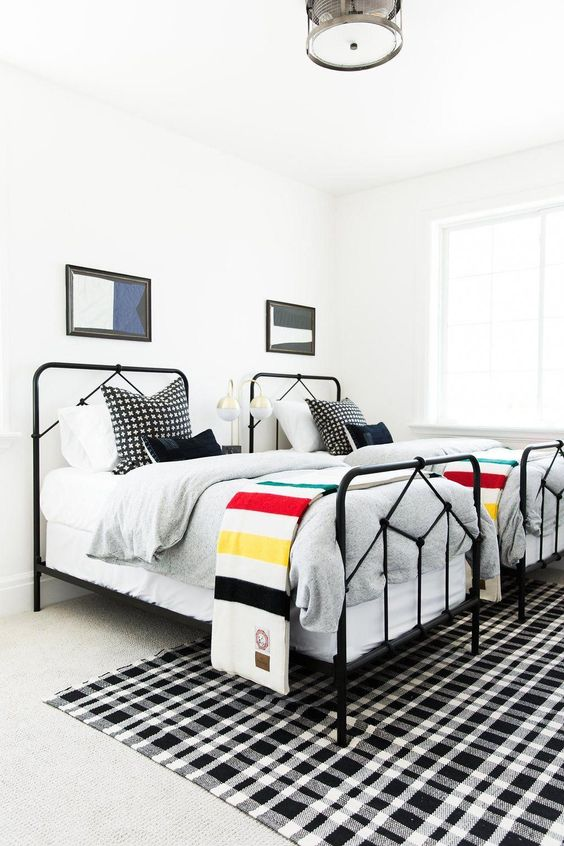 a bright shared boy bedroom with white walls, black beds, layered rugs and bright graphic bedding