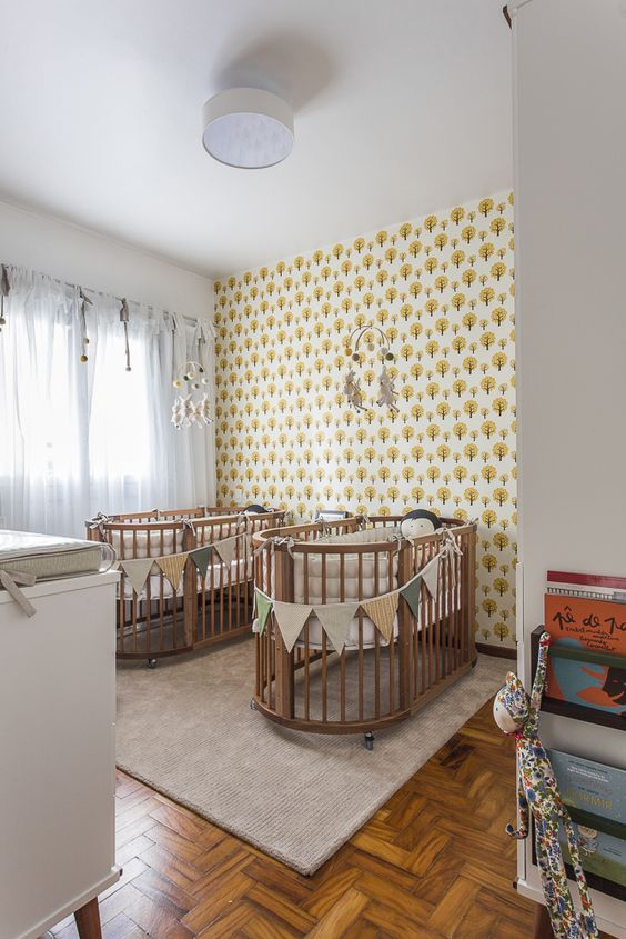 a bright shared nursery with printed wallpaper, stained cribs and neutral furniture, colorful fabric buntings and mobiles