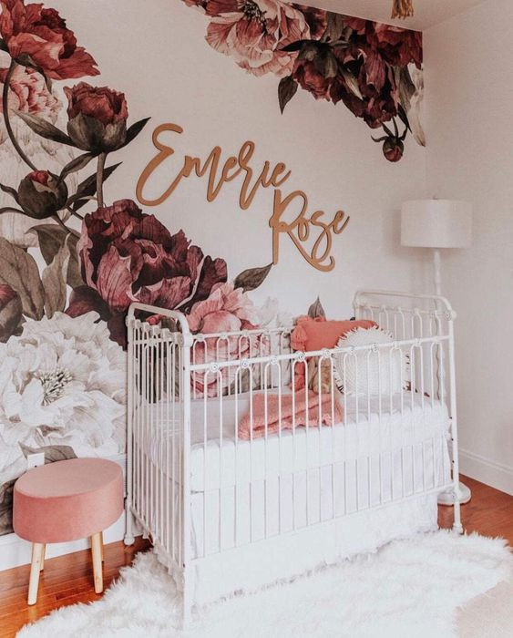 a chic girl nursery with a bold floral mural on the wall, white furniture, a pink stool and white and coral bedding